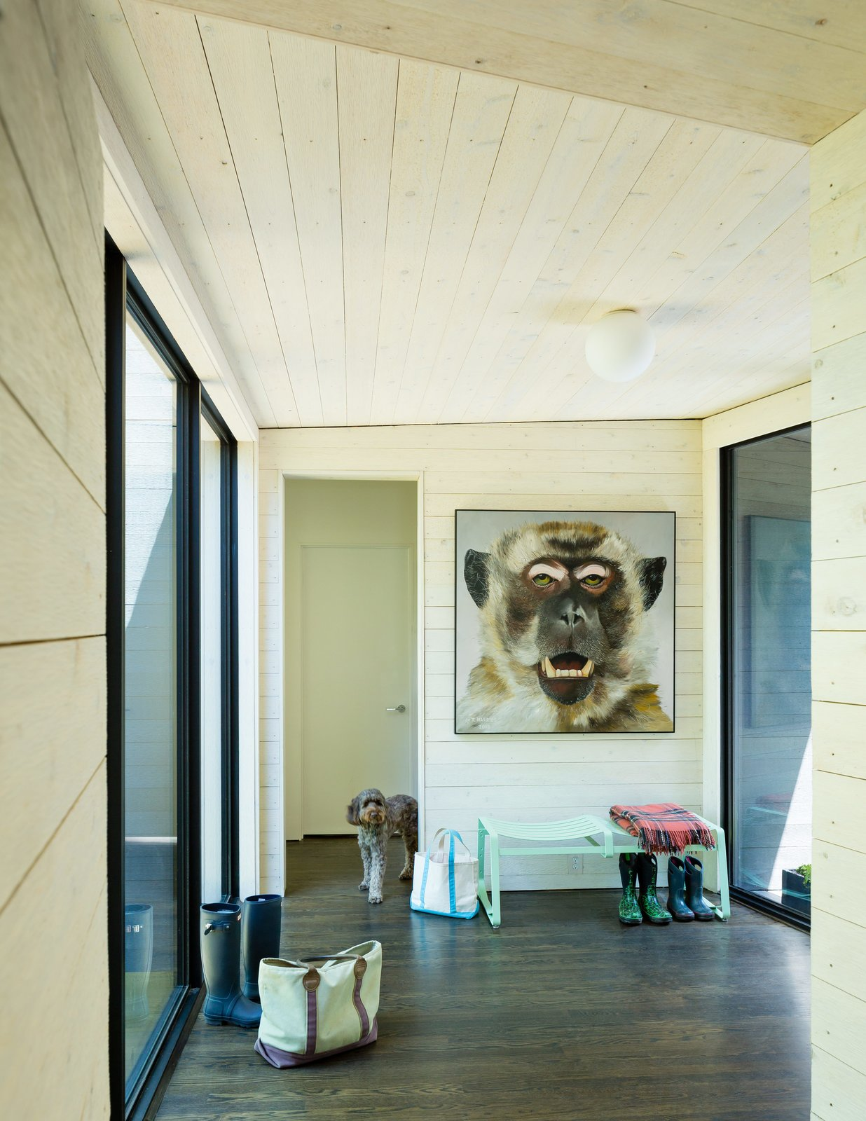Hallway and Medium Hardwood Floor ARCHITECTUREFIRM used rough-sawn cedar paneling throughout, cladding the exterior with blackened pieces, and whitewashing the interior surfaces to form a dramatic visual contrast between inside and out. A painting by artist Tim Harriss hangs above a Crane bench by Double Butter near the entry hall.  Photo 5 of 9 in Three Joined Cabins Turn This Virginia Retreat Into a Modern Take on Camp