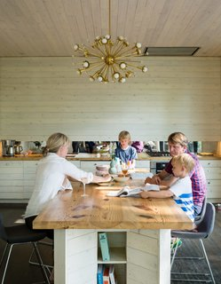 The kitchen island, designed by ARCHITECTUREFIRM and custom-fabricated with pine by Peter Johnson Builders, doubles as a dining table. It's paired with Inmod barstools, and a brass-and-crystal Sputnik chandelier by Jonathan Adler, which hangs overhead.