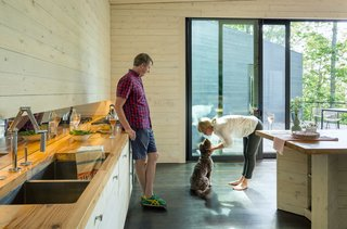 Three Joined Cabins Turn This Virginia Retreat Into a Modern Take on Camp - Photo 5 of 8 - Uses for the three rectilinear pavilions are distinctly categorized: The dining room and kitchen are located in the central volume; a guest bedroom and media room are situated in the west wing; the master bedroom and a bunk room, for the boys, are in the east wing.