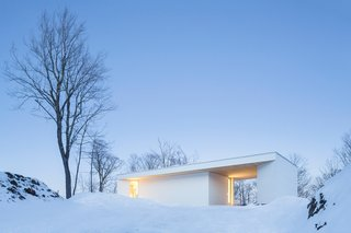 Seen from the street, the Nook Residence's white-painted wood exterior vanishes against a snowy backdrop.