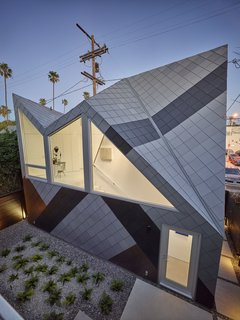 """Concerned that studio was too big compared to other homes in the neighborhood, the 1,060 square-foot structure references the dazzle pattern, a camouflage technique used by WWII battleships. Monti was inspired by the way the pattern """"helps break down the scale of a large ship."""" Modal Design choose the zinc colors that fit with the neighborhood. """"From afar and at certain angels, it is hard to see where one starts and one ends."""" says Monti."""