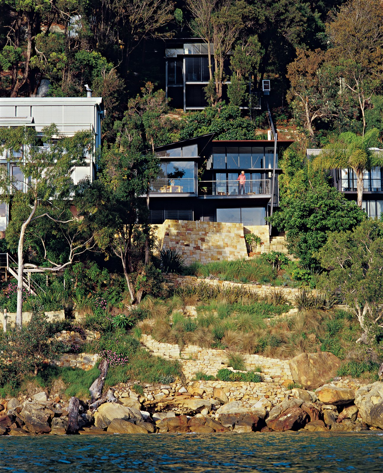 Outdoor, Slope, Trees, Shrubs, and Boulders Set high on a cliff along the south end of the beach, this residence of three glass-and-copper pavilions offers a mighty reward for conquering the steep ascent.  Photo 5 of 11 in Three Glass-and-Copper Pavilions Conquer the Cliffs