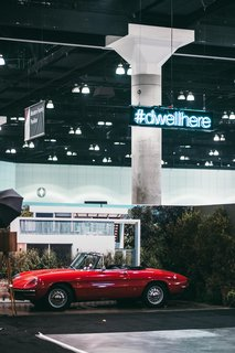 """Sitting in front of an enlarged photograph of a house in Venice from the June 2016 issue is a 1966 Alfa Romeo Duetto Spider provided by the Petrolicious Marketplace. Make sure to share your favorite moments from the show by using<span> <a href=""""/discover/dwellhere"""">#dwellhere</a></span>—we'll be doing the same."""