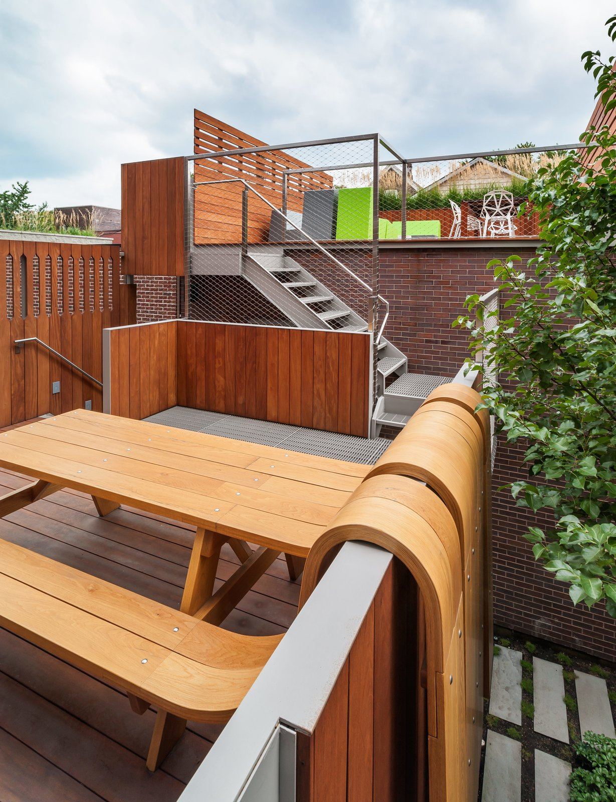 Outdoor, Rooftop, Vertical Fences, Wall, Wood Fences, Wall, Wood Patio, Porch, Deck, and Horizontal Fences, Wall A sculptural picnic table by artist Michael Beitz flows over the fence like a waterfall.  Photo 7 of 17 in Four Floors of Gadgets and Gardens in Chicago