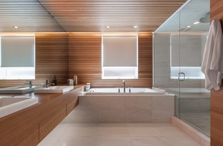 The bathrooms saw the least significant changes. In the one nearest to the master bedroom, the shower and tub are original. White oak paneling provides continuity between the newly renovated spaces.
