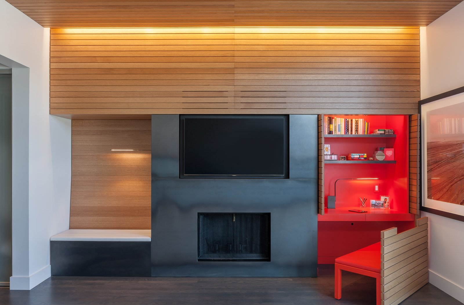 Living Room, Ceiling Lighting, Dark Hardwood Floor, Bench, and Standard Layout Fireplace In the office, doors slide back and a chair pulls out to reveal a custom built-in desk.  Photo 10 of 17 in Four Floors of Gadgets and Gardens in Chicago