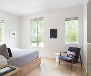 The house is well-equipped for guests, with multiple sleeping areas. The main guest room features a custom reclaimed oak bed by BenchCraft and a Callan chair from Room & Board.