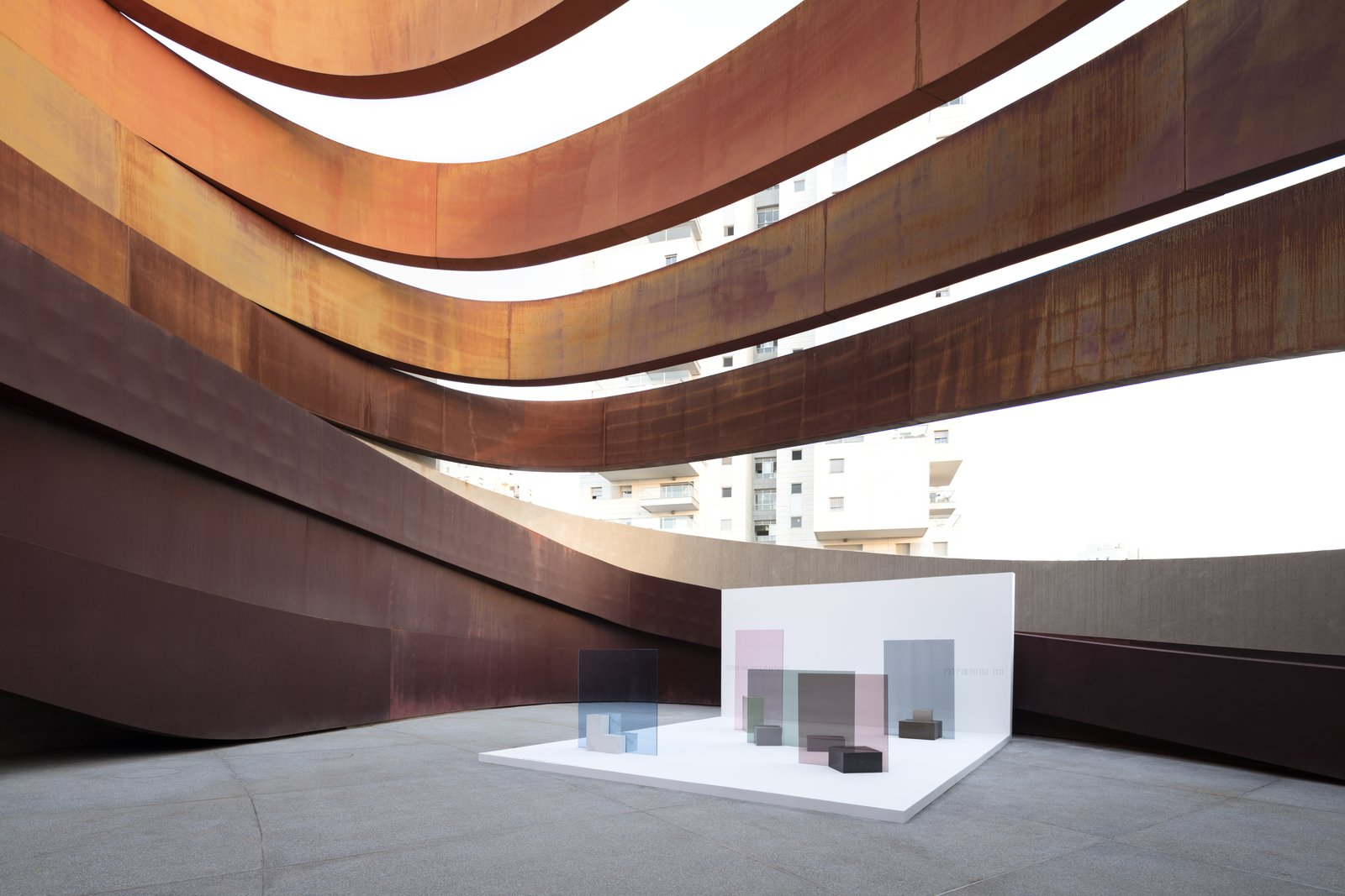 The work's overlapping layers of color and transparency respond to the patterns of light and shade created by the surrounding architecture.  Photo 4 of 8 in Nendo's Minimalism Meets Ron Arad's Sweeping Curves