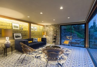 The interior is defined by material combinations that are as entrancing as the view. Ceramic tile flooring pairs with local stone walls in the living room.