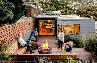 After raising the rear patio to the level of the kitchen, the team reused the original redwood decking and supplemented it with recycled pieces from other projects. Recessed planters punctuate a garden wall. Scott and Regina warm themselves by a Solus fire pit on chilly evenings.