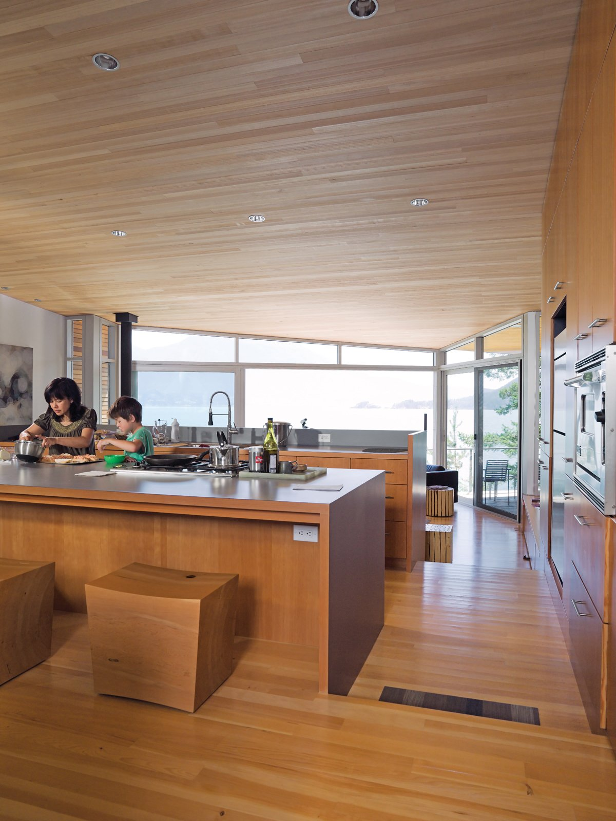Kitchen, Wood Counter, Recessed Lighting, Medium Hardwood Floor, and Range Lam and her son Max prepare a snack together in the open-plan kitchen at the center of the house. The fir floor that covers the living space steps downward twice, creating a grade change that roughly follows the topology of the site. The ceiling is sheathed in untreated hemlock; the custom stools were designed by Brent Comber.  Photo 5 of 9 in When Living on the Edge is Super Comfortable
