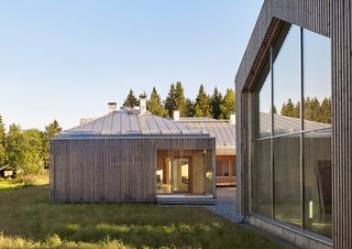 "The home comprises three structures: a main house, a garage, and a studio for resident Elina Försti, an artist. Local spruce cladding, metal standing-seam roofs, and aluminum frames mean the entire complex is recyclable. ""Right now, it all looks very polished, but in the future it will develop a nice patina,"" Lassila says."