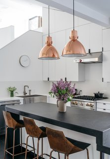 The kitchen is outfitted with a granite countertop and custom casework; the hardware is by Tom Kundig. Richard and his wife, Kristine, sourced the pendants from Craigslist, then had them plated in copper. The appliances are by Viking, and the bar stools are Real Good chairs by Blu Dot.
