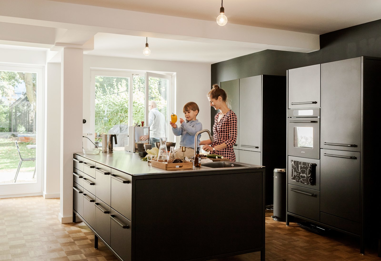Kitchen, Refrigerator, Wall Oven, Cooktops, Colorful Cabinet, Ceiling Lighting, Pendant Lighting, and Medium Hardwood Floor  Photo 1 of 12 in We Can't Get Enough of This German Apartment's Sleek Matte-Black Kitchen