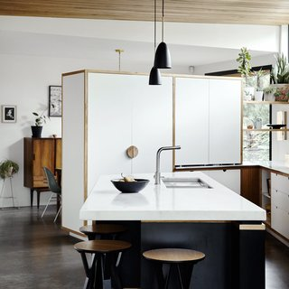 """Using laminates trimmed in Victorian ash for the island cut costs. The white cabinets hide the refrigerator<span style=""""line-height: 1.8;"""">and separate the kitchen from the dining room.</span><span style=""""line-height: 1.8;""""></span>"""