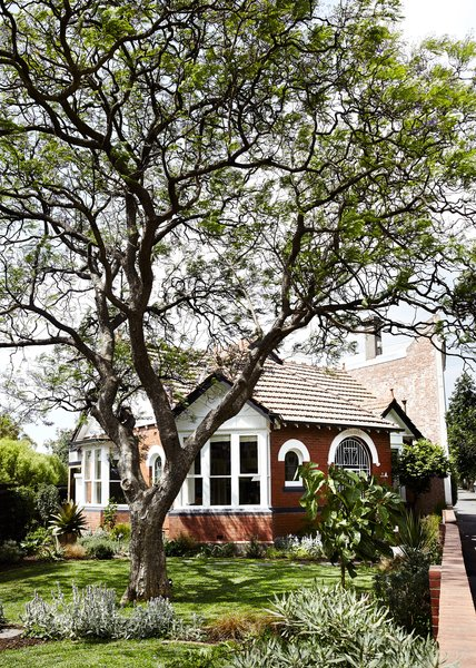 The house is located on a tight site surrounded by a brick wall.  Photo 7 of 13 in An Unassuming Edwardian Saves the Best for Out Back