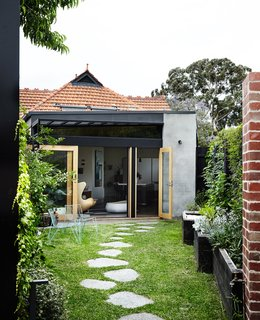 On the back facade, cement render and black-painted steel update the existing terra-cotta roof tiles. Custom glass doors fabricated by TCM Building Group open onto the garden, where a stone path leads to a new building housing Kate's studio and Tom's wine cellar.