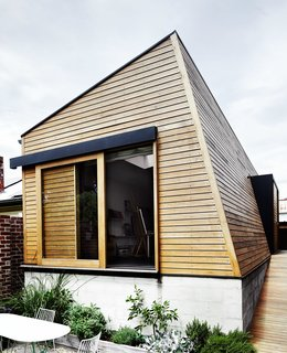 An angular new outbuilding fills the footprint of what was once an inground swimming pool, completing an awkward corner at the back of the site.