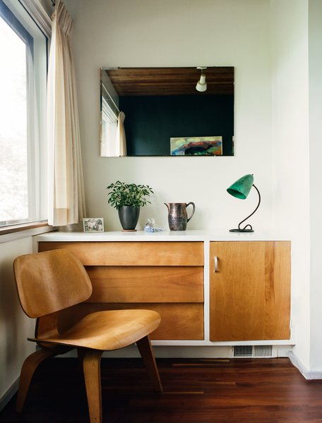 Medium Hardwood Floor Built-in details include a dresser that pairs with an Eames molded plywood lounge chair in a guest bedroom.  Photo 6 of 16 in Kansas City Royal