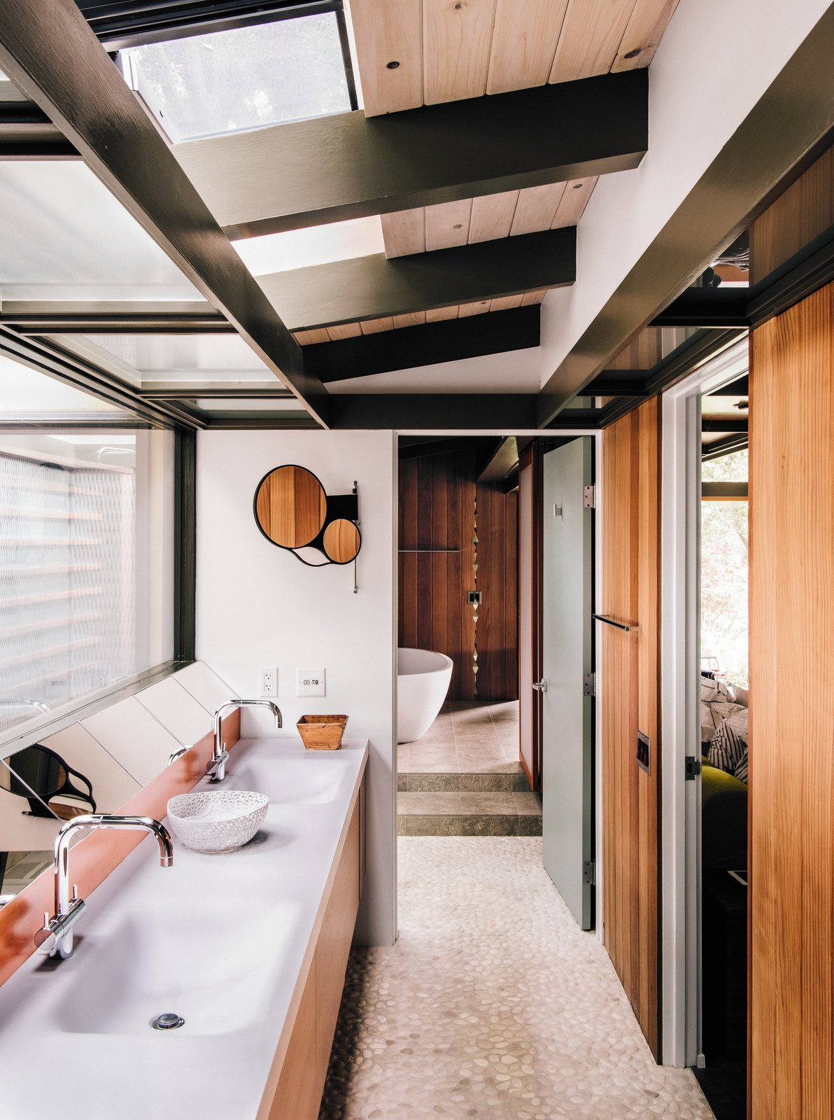 Bath Room and Freestanding Tub Fung + Blatt designed the master bathroom vanity, which features Agape washbasins and fixtures and an angled mirror that reflects the oak trees seen through the skylights.  Photo 5 of 14 in Creative Revival of a Modernist Gem