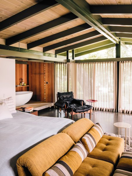 A tub zone lined in redwood connects to the master bedroom, which is furnished with a vintage Sergio Rodrigues lounge chair and Voyage Immobile seats from Roche Bobois.