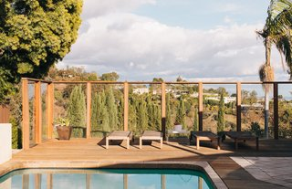 """<span style=""""line-height: 1.8;"""">Contractor Roderick McGrew was tasked with removing the massive A-frame structure that the former owners had added to enclose the rear patio and the pool. """"Removing it took three times as long as we thought it would,"""" Tyler recalls. McGrew also redid the deck and installed wood floors throughout the interior.</span>The deck commands panoramic views of the city and the ocean in the distance. The lounge chairs are from IKEA."""