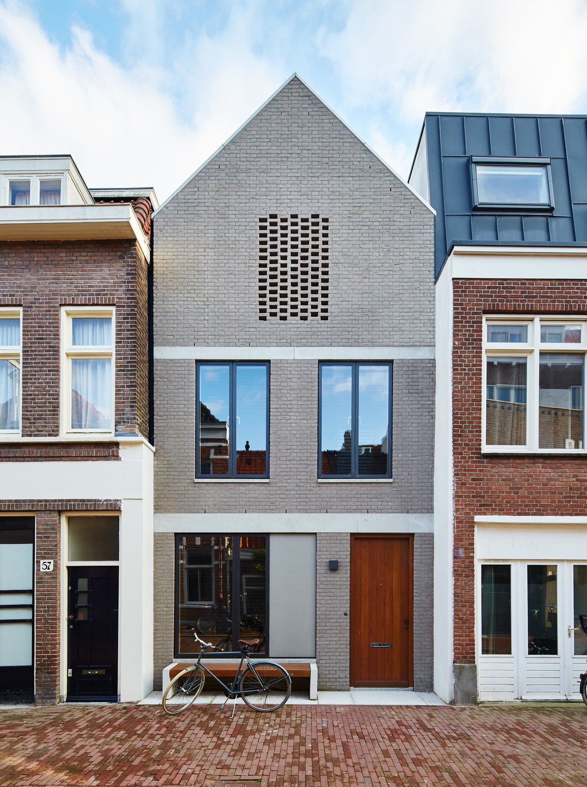 Exterior, House Building Type, Brick Siding Material, and Gable RoofLine By setting an Amsterdam house a few feet back from the street, 31/44 Architects ensured the city's planning department that the new construction would not block light to the surrounding structures. The gray brick facade references the building material of choice in the formerly industrial neighborhood, which has seen a residential resurgence.  Photo 2 of 11 in New Kid on the Block
