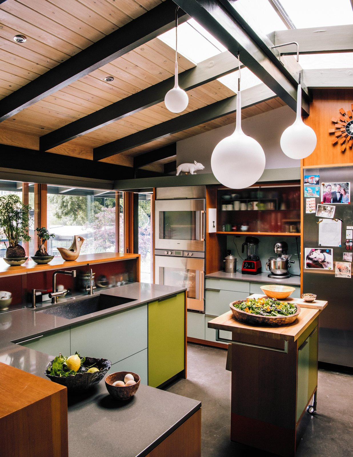 Kitchen, Undermount Sink, Wall Oven, Cooktops, Refrigerator, Wood Counter, Colorful Cabinet, Concrete Floor, Ceiling Lighting, and Pendant Lighting  Photo 2 of 14 in Creative Revival of a Modernist Gem