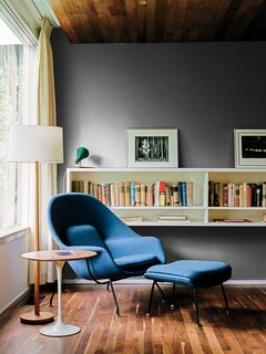 A walnut-topped table and Womb chair, both by Eero Saarinen for Knoll, offer a cozy spot for reading.