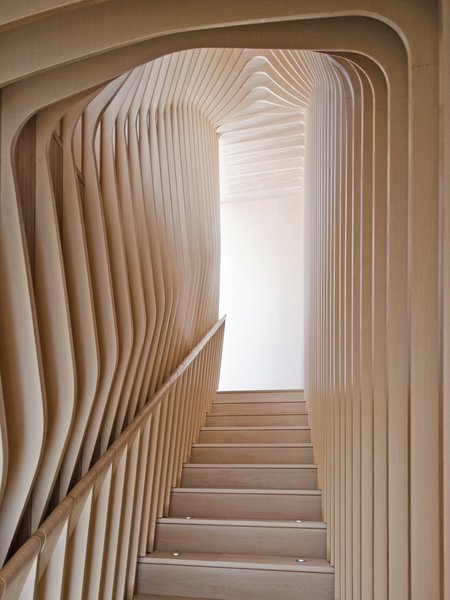 Organic, undulating forms frame the stairwell that connects the first floor and garden floor. Though they give the appearance of bent plywood, each curved layer of the ribbed corridor was constructed with flat, laminated cutouts, including the rounded hand rail.