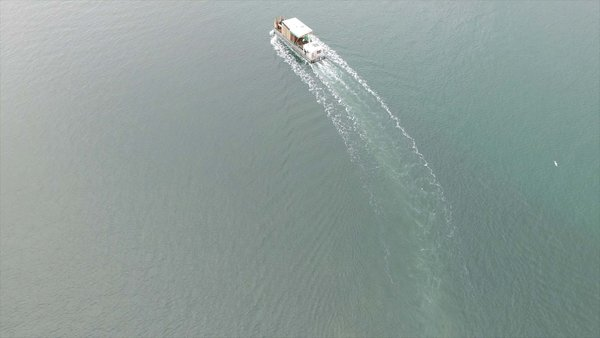Captured by drone, this photograph shows the prefabricated elements of the Brown house being transported to the build site on French Island by barge.