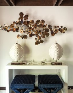 Nearby, the Lacquer Console Table holds a pair of Ceramic Tortoise Shell lamps and conceals a Double X bench, also by the designer (below). The brass Raindrops wall sculpture, a reissue of a midcentury metalwork by C. Jeré Studio, is from JA Finds, Adler's curatorial venture.