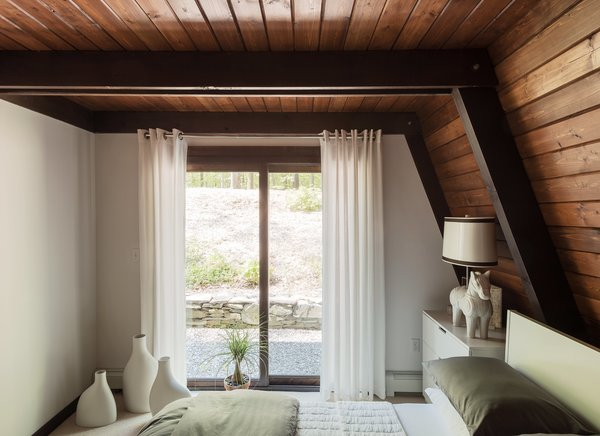 The guest bedrooms feature lighting by Jonathan Adler, including a Horse table lamp in the downstairs unit and an Antwerp pendant upstairs.  Photo 10 of 12 in One Couple's Imagination Goes Wild at a 1967 Weekend Retreat