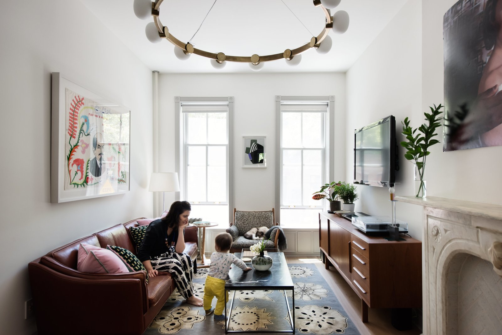 Living Room, Sofa, Pendant Lighting, Ceiling Lighting, Table Lighting, Console Tables, End Tables, Coffee Tables, Lamps, Rug Floor, and Light Hardwood Floor Interior designer Merrill Lyons plays with her son in the Brooklyn home she renovated with her husband, Charles Brill, a lighting designer and cofounder of New York–based company Rich Brilliant Willing (RBW). The couple's design sensibility is marked by a warm mix of historic periods and styles, punctuated with pieces by RBW, including the circular brass Cinema chandelier that hangs in the living room. The leather sofa and teak  credenza are vintage; the 1960s rosewood Genius armchair by Danish designer Illum Wikkelso was reupholstered with fabric sourced from an outlet.  Photo 2 of 14 in Modern Becomes Eclectic in This Renovated Brooklyn Townhouse