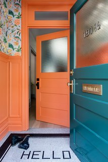 The vestibule is painted in Benjamin Moore's coral-hued Hot Spice and covered in a Cuban-inspired floral wallpaper by fashion designer Matthew Williamson for Osborne & Little.