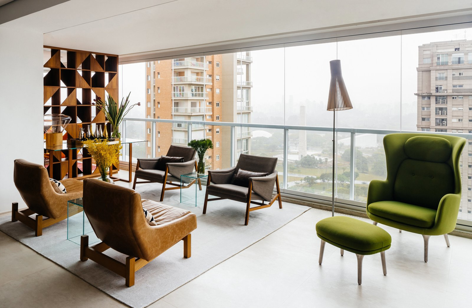 Living Room, Chair, Recliner, Console Tables, Coffee Tables, End Tables, Table Lighting, Lamps, and Rug Floor In an apartment overlooking São Paulo's Ibirapuera Park—completed in 1954 to commemorate the city's 400th anniversary—the furniture is as distinctive as the view. Architect Flavio Castro of FCstudio worked closely with the residents to update and outfit the home, which is appointed with a mix of contemporary and Brazilian modern classics. A pair of Sérgio Rodrigues's Paraty armchairs (in foreground)—designed for Brasilia's Itamaraty Palace in 1963—face a duo of Jader Almeida's Isa armchairs in the living area. The green Ro lounge and ottoman are by Jaime Hayon for Fritz Hansen.  Photo 1 of 9 in Overlooking a Niemeyer Masterpiece, This Flat is Filled with Brazilian Modern Gems