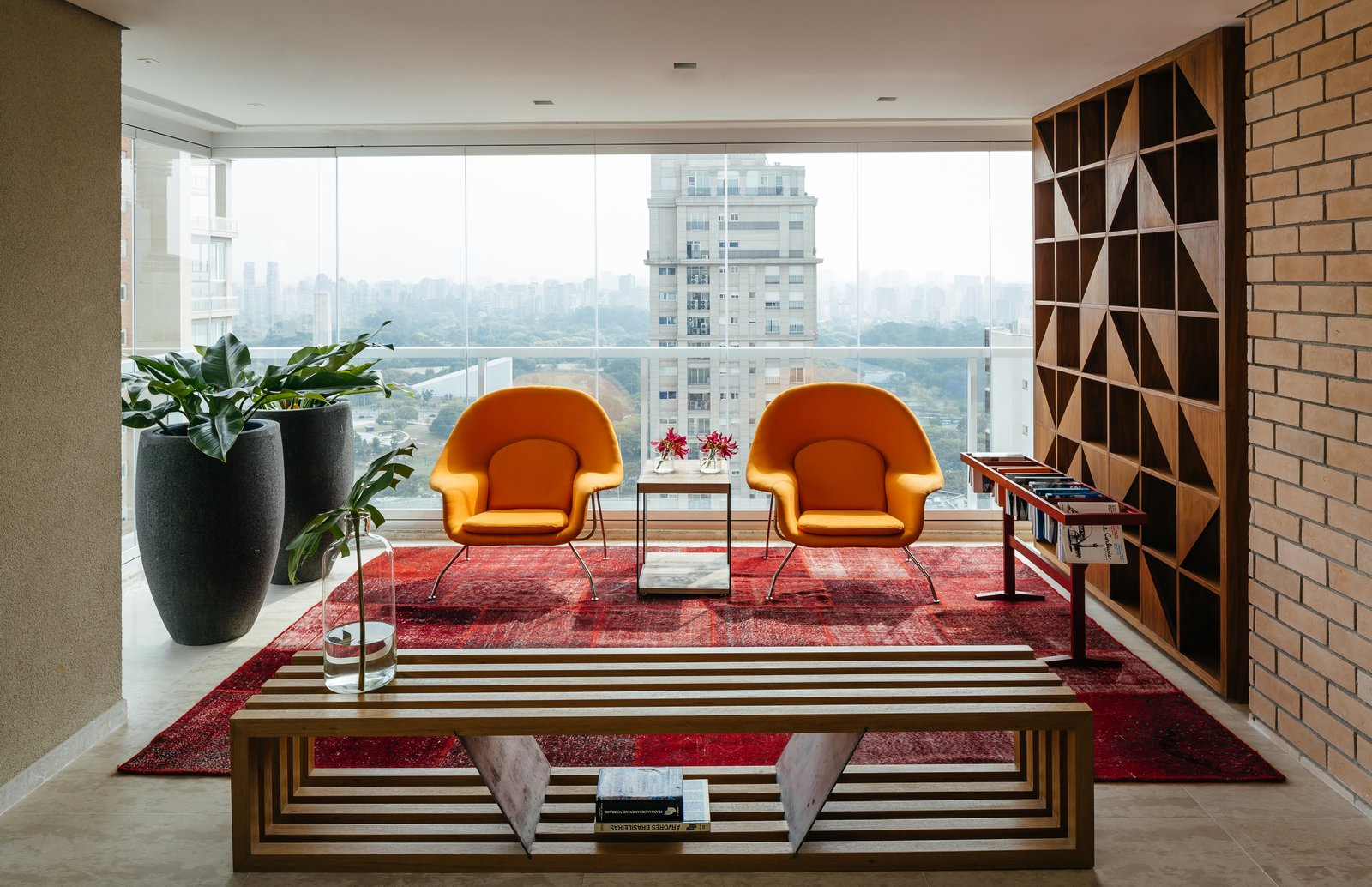 Two Womb chairs by Eero Saarinen for Knoll and a Ring bench by Castro structure a reading area in the enclosed terrace. Tagged: Living Room, Chair, Bench, Console Tables, Coffee Tables, End Tables, Table, Ceiling Lighting, Recessed Lighting, and Rug Floor.  Photo 2 of 9 in Overlooking a Niemeyer Masterpiece, This Flat is Filled with Brazilian Modern Gems