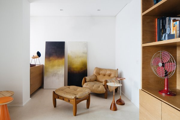 Chair and Storage An original 1961 Mole armchair and ottoman—an iconic Sérgio Rodrigues design made from oversize tufted leather cushions and rounded wood frames—sits in the office.  Photo 5 of 9 in Overlooking a Niemeyer Masterpiece, This Flat is Filled with Brazilian Modern Gems
