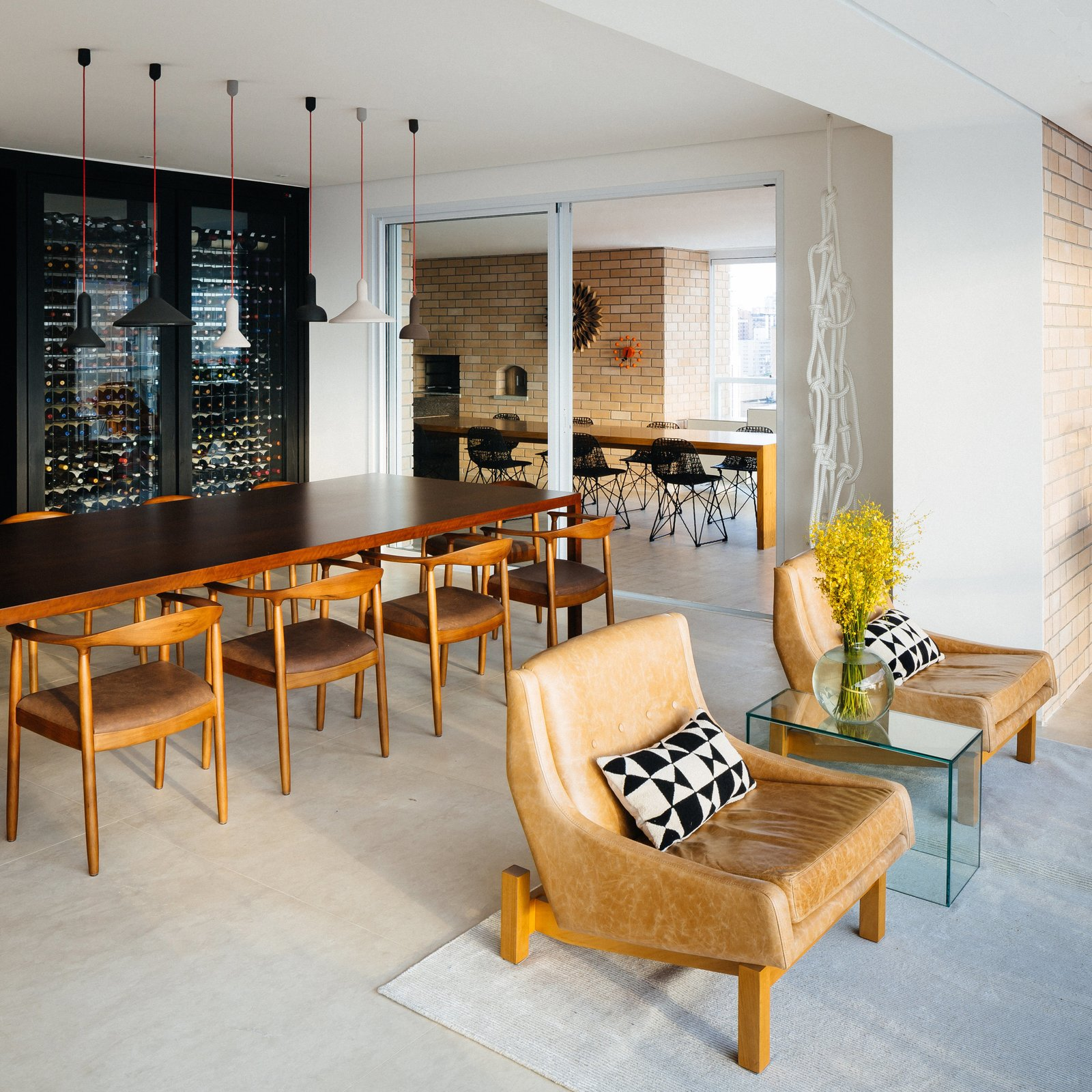 Dining Room, Chair, Table, Bar, Storage, Shelves, Ceiling Lighting, Pendant Lighting, and Rug Floor In the dining area, a custom wine rack doubles as a partition for the open plan. The adjacent door leads to an expansive enclosed terrace.  Photo 6 of 9 in Overlooking a Niemeyer Masterpiece, This Flat is Filled with Brazilian Modern Gems