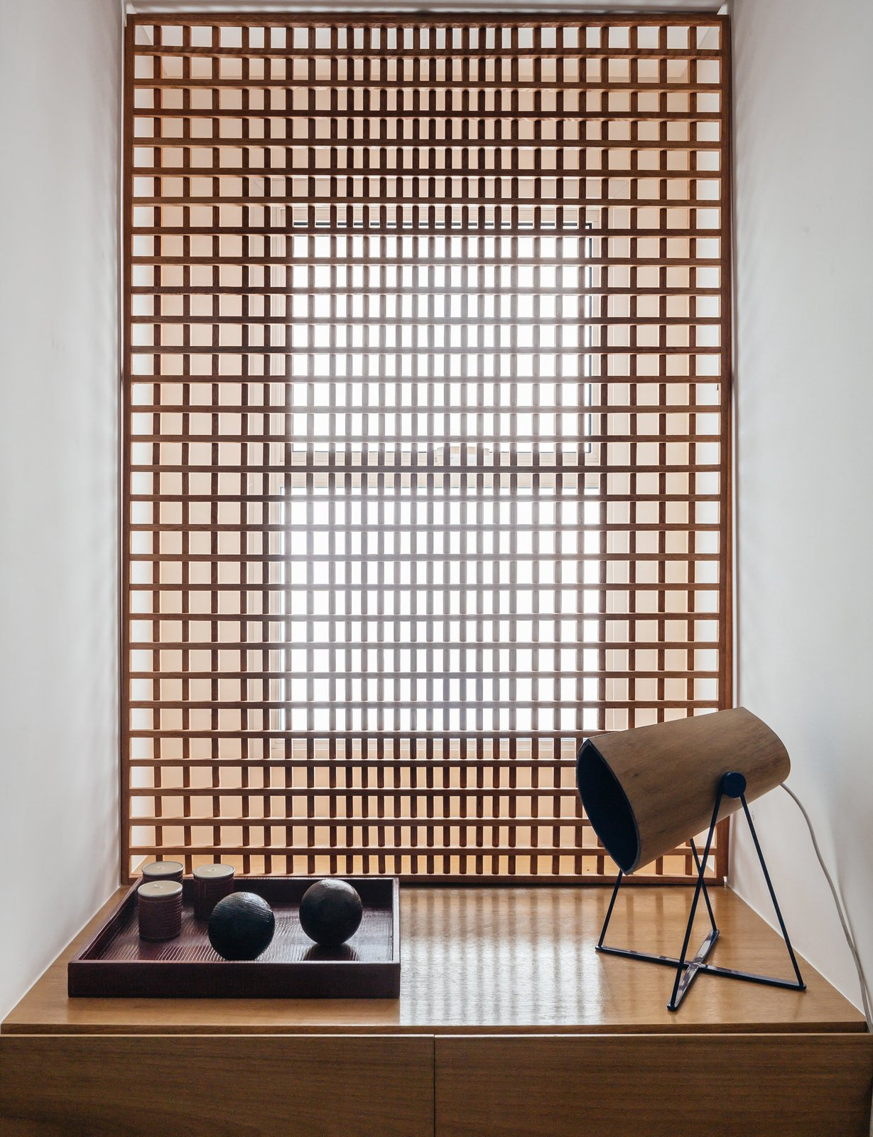 Living Room, Storage, Lamps, and Table Lighting FCstudio designed the gridded Muxarabi panel made of catuaba wood; placed in front of the home office window, it softens light to a diffuse glow.  Photo 7 of 9 in Overlooking a Niemeyer Masterpiece, This Flat is Filled with Brazilian Modern Gems