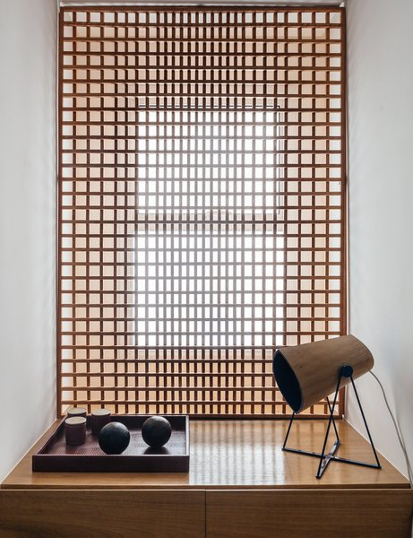Storage FCstudio designed the gridded Muxarabi panel made of catuaba wood; placed in front of the home office window, it softens light to a diffuse glow.  Photo 7 of 9 in Overlooking a Niemeyer Masterpiece, This Flat is Filled with Brazilian Modern Gems