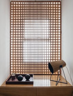 FCstudio designed the gridded Muxarabi panel made of catuaba wood; placed in front of the home office window, it softens light to a diffuse glow.