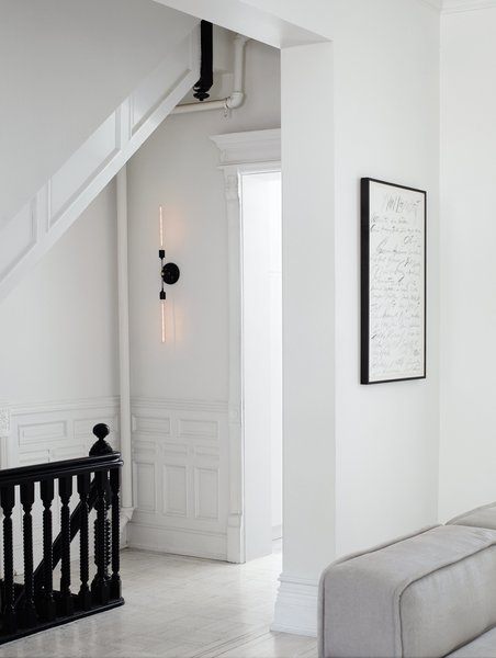 After restoring and renovating the interior of their four-story brownstone in Brooklyn's Bedford-Stuyvesant neighborhood, Jeff Madalena and Jason Gnewikow—creative entrepreneurs and self-described interiors obsessives—outfitted the historic 1910 space with a minimal black-and-white palette, down to the stair railing and original moulding and wainscoting. Sparse, modern pieces—like a two-pronged sconce they designed for the parlor-floor landing and a Cy Twombly print in the adjacent family room—provide elegant counterpoints to the architecture.  Photo 1 of 10 in A Fashionable Couple Remake Their Brooklyn Brownstone with a Sartorial Twist
