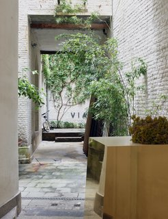 A golden-mirrored Formica piece, presented at Milan Design Week in 2014, punctuates the brick-and-stucco courtyard.