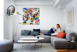 A Danish Design Kingpin Moves to NYC with a Shipping Container of Furniture in Tow - Photo 1 of 13 - The New York loft of Muuto cofounder Peter Bonnén showcases a shipping container's worth of furniture from Denmark. His wife, Jasmi, relaxes among Muuto designs, including a Connect sofa by Anderssen & Voll and Airy tables by Cecilie Manz. The wall sculpture is by artist Anders Kappel; the painting is by Peter's brother, Kaspar.
