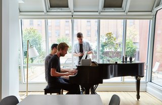 Peter and two of his U.S. colleagues gather around the Steinway piano.