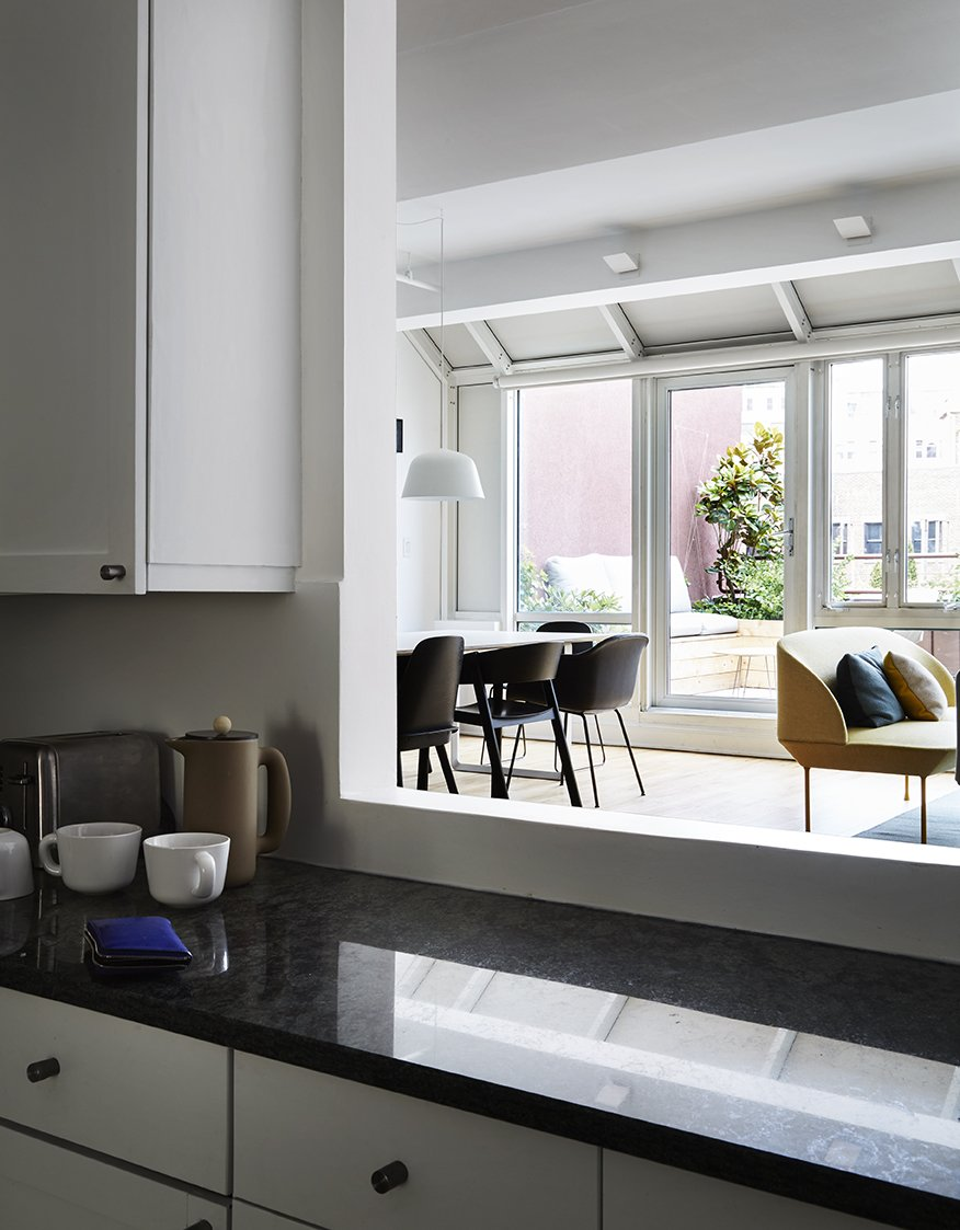 An opening in the kitchen wall allows a view of the terrace from behind the black marble counter. Tagged: Kitchen, White Cabinet, and Marble Counter.  Photo 7 of 14 in A Danish Design Kingpin Moves to NYC with a Shipping Container of Furniture in Tow