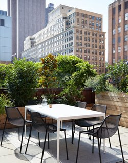 The Bonnéns have planters on each of their three terraces, which provide them with tomatoes, herbs, and more. Their outdoor dining area includes a Porcelain table by Richard Schultz for Knoll, Round chairs by Christophe Pillet for Emu, and a wool Ply rug by Margrethe Odgaard for Muuto.