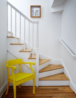In the hallway, a yellow Raw chair by Jens Fager for Muuto pops against the white staircase.