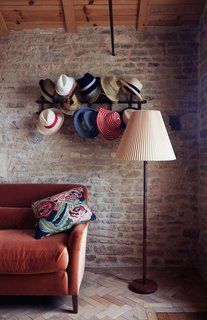 "In a cozy nook the family calls the ""snug,"" hats hang from a Thonet rack above a Noelle sofa by Pinch, which is upholstered in orange velvet by Kravet."